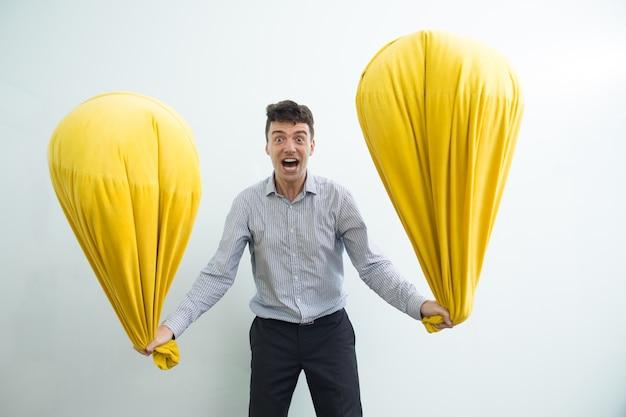 Homem furioso de idade média girando dois almofadas