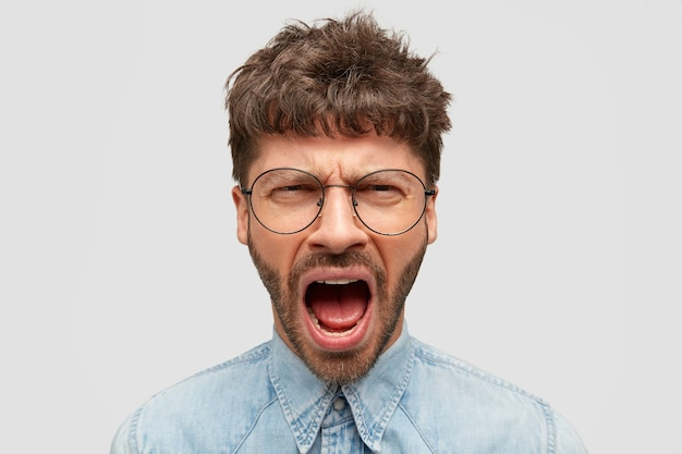 Homem furioso grita furiosamente, mantém a boca bem aberta, sente uma dor terrível, vestido com uma camisa jeans