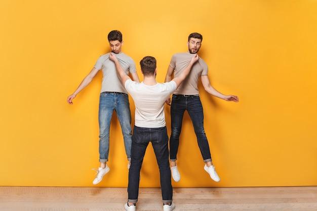 Homem furioso segurando dois outros homens pelo colarinho