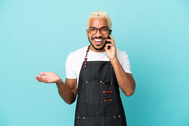 Homem garçom colombiano de restaurante isolado em fundo azul conversando com alguém ao telefone celular