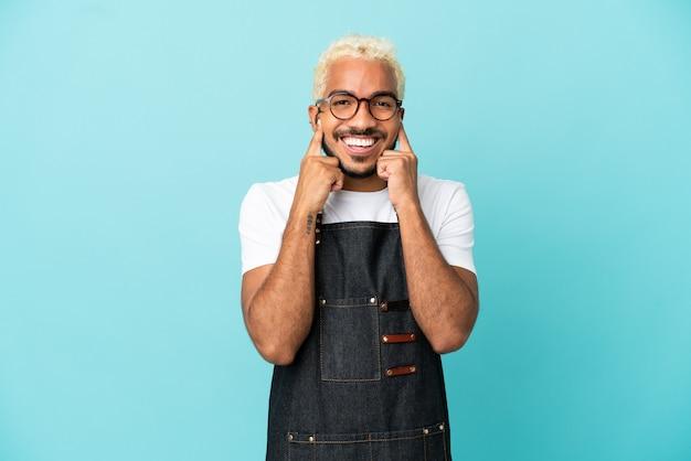 Homem garçom colombiano isolado em um fundo azul sorrindo com uma expressão feliz e agradável