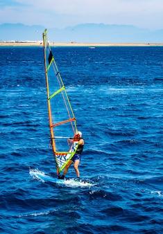 Homem gastando lazer com esporte radical de windsurf no mar azul com praia de areia ao fundo