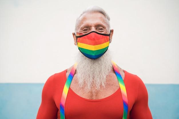 Homem gay sênior feliz usando máscara do orgulho com a bandeira do arco-íris
