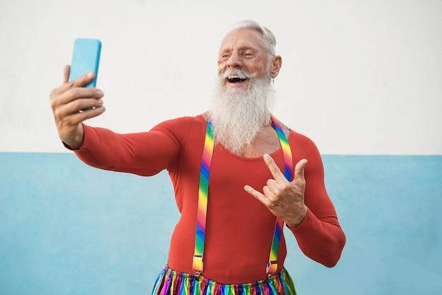 Homem gay sênior usando telefone celular durante protesto do orgulho lgbt - foco no rosto