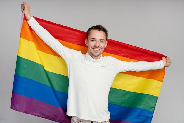 Homem gay sorridente com bandeira de arco-íris