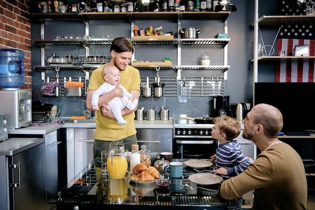 Homem gay sorridente e feliz apresentando o bebê recém-nascido a seu filho mais velho no café da manhã em família