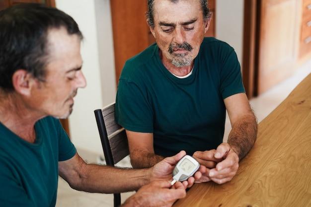 Homem gêmeo sênior faz teste de glicemia para irmão para diabetes em casa - concentre-se no homem certo