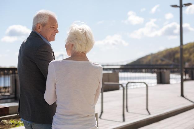 Homem gentil sênior feliz sentindo felicidade enquanto descansa e discute o dia com sua esposa
