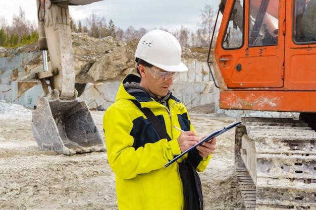 Homem geólogo ou engenheiro de minas escreve algo em uma caixa de mapa em meio a uma pedreira com equipamentos de construção