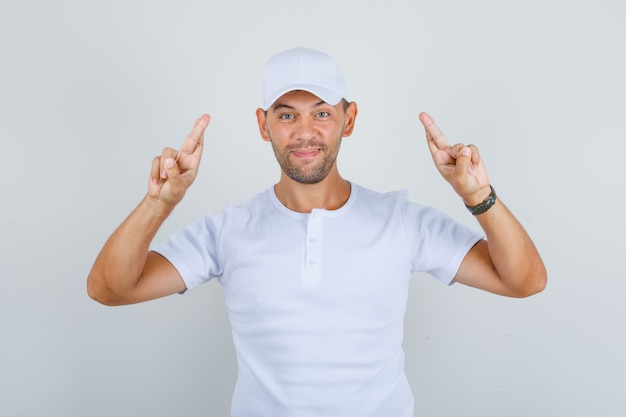 Homem gesticulando com o dedo cruzado e desejando sorte na camiseta branca, boné e parecendo feliz, vista frontal.