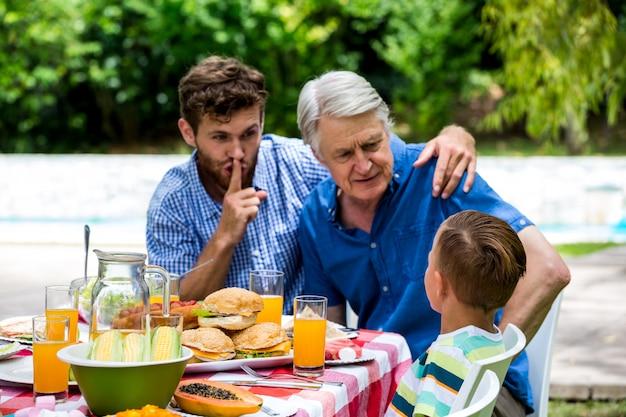Homem gesticulando silêncio enquanto filho conversando com o avô no gramado