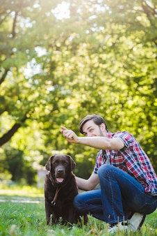 Homem, gesticule, enquanto, tendo divertimento, com, seu, cão, parque