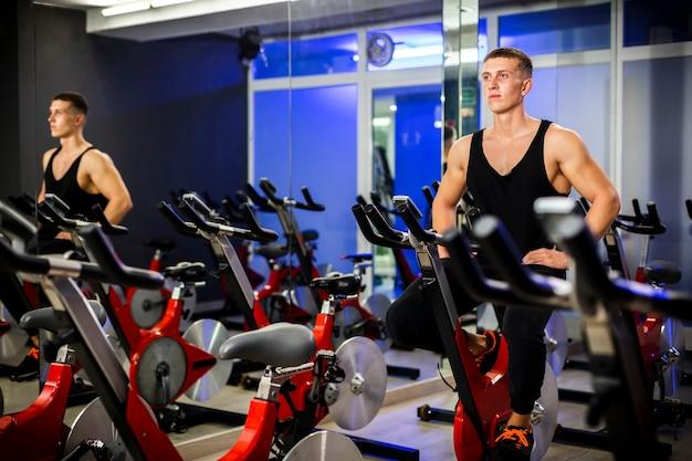 Homem girando em uma bicicleta em uma academia