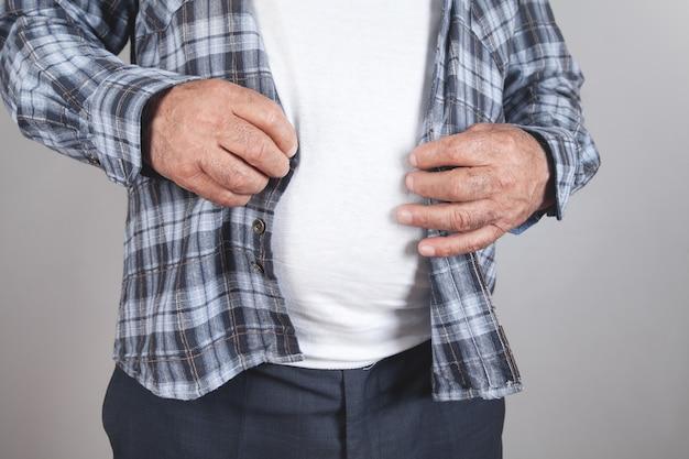 Homem gordo apertando botões na camisa em fundo cinza.