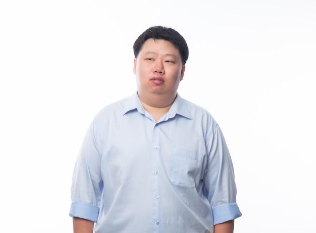 Homem gordo asiático de camisa azul, pensando e olhando para copyspace isolado no fundo branco