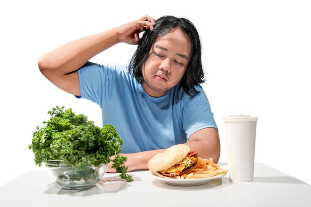 Homem gordo asiático novo confuso escolhendo entre fast food ou alimentos saudáveis
