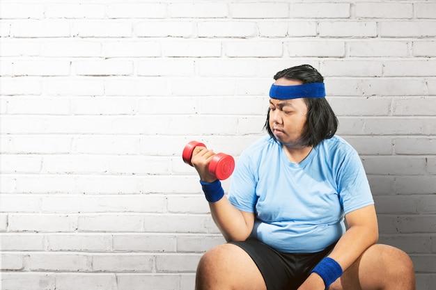 Homem gordo asiático usando halteres para perder peso