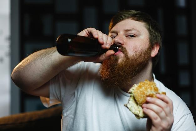Homem gordo assiste tv, come hambúrguer e bebe cerveja