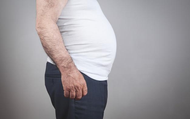 Homem gordo caucasiano com barriga grande em fundo cinza.
