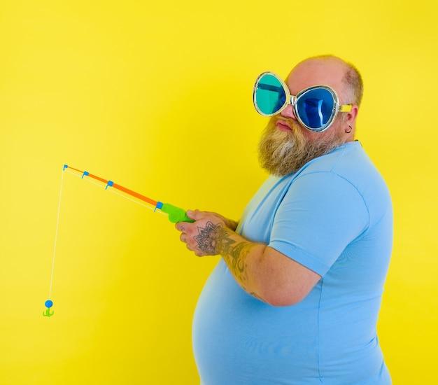 Homem gordo com barba e óculos escuros insatisfeito com a vara de pescar