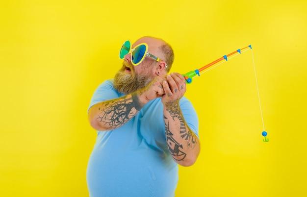 Homem gordo com barba e óculos escuros se diverte com a vara de pescar