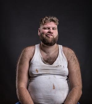Homem gordo com barba na camisa suja