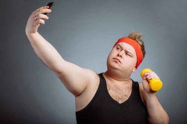 Homem gordo com barriga grande, segurando halteres, fazendo selfie na parede cinza