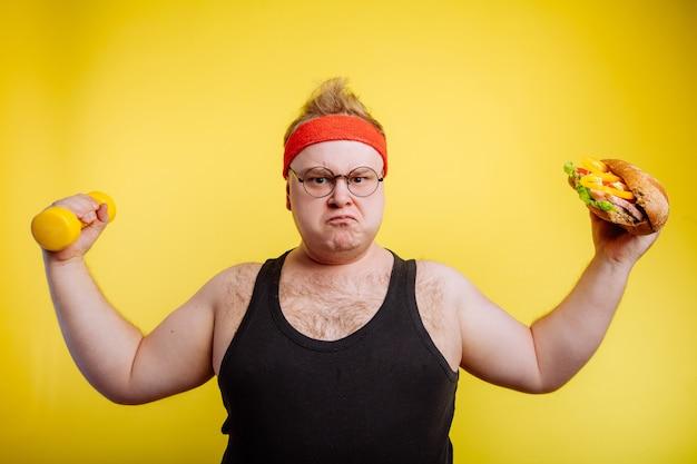 Homem gordo com fome, mostrando o bíceps com hambúrguer e halteres