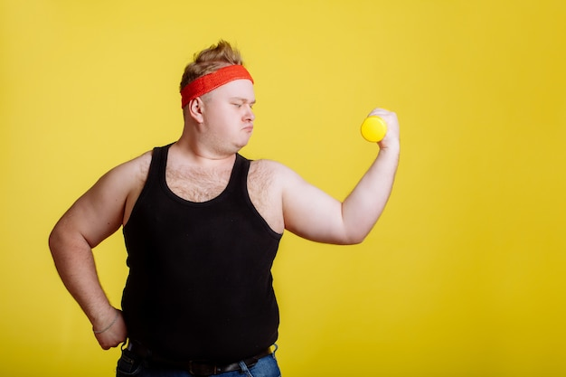 Homem gordo com halteres na parede amarela. motivação para pessoas gordas