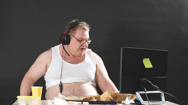 Homem gordo com óculos e fones de ouvido, sentado em uma mesa, comendo e jogando um jogo de pc em casa. auto-isolamento, quarentena