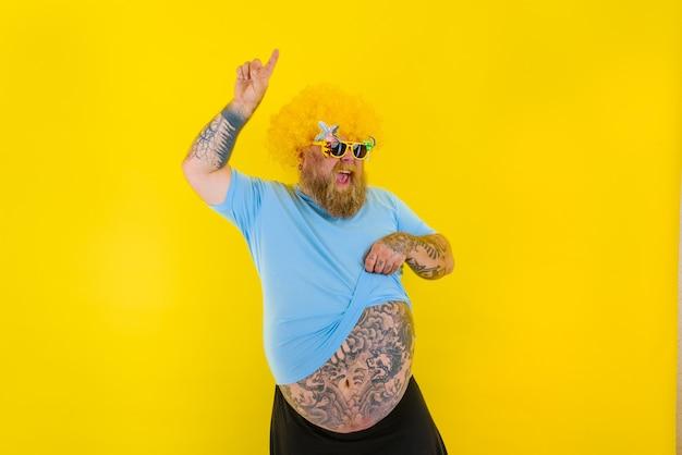 Homem gordo com peruca na cabeça e óculos escuros dançando