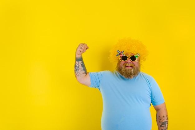 Homem gordo com peruca na cabeça e óculos escuros mostra seus músculos