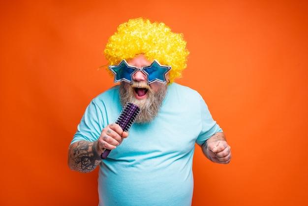 Homem gordo com tatuagens de barba e óculos de sol canta uma música