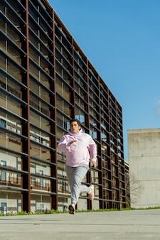 Homem gordo correndo pelo centro da cidade ao meio-dia, usa roupas esportivas