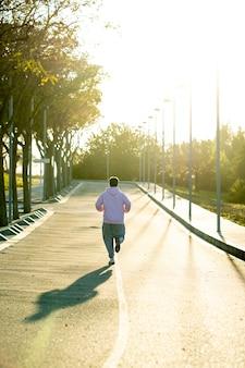 Homem gordo de costas correndo colina acima no meio da rua