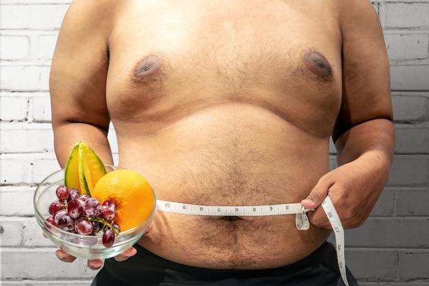 Homem gordo, dieta, com, fruta, usando, medindo fita, para, medindo, seu, estômago