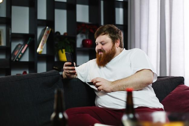 Homem gordo digita o número de um cartão de crédito em seu telefone sentado no sofá