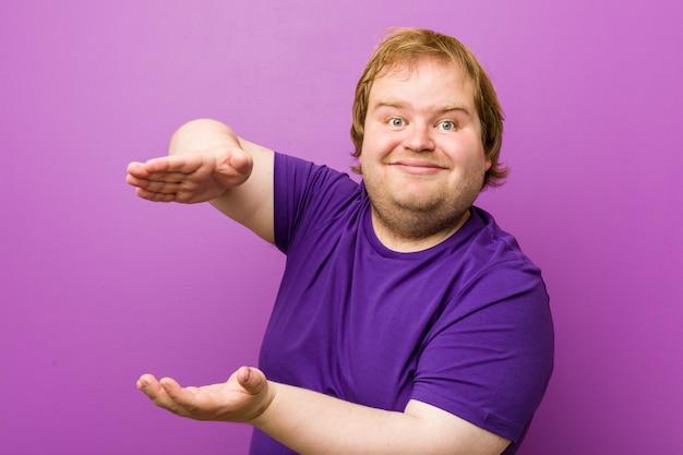 Homem gordo do ruivo autêntico novo que guarda algo com ambas as mãos, apresentação do produto.