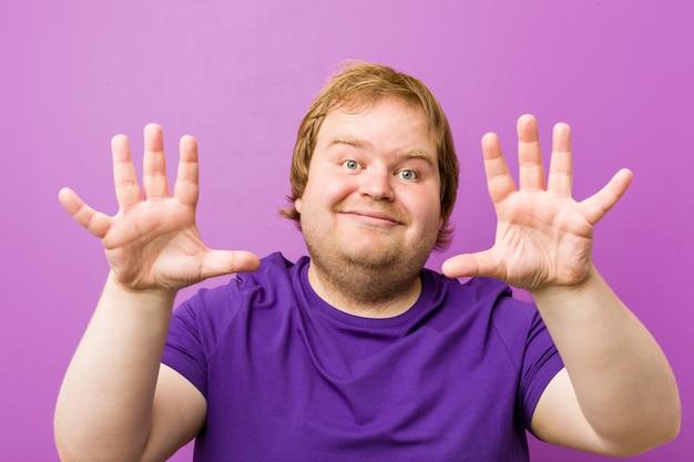 Homem gordo do ruivo autêntico novo que mostra o número dez com mãos.