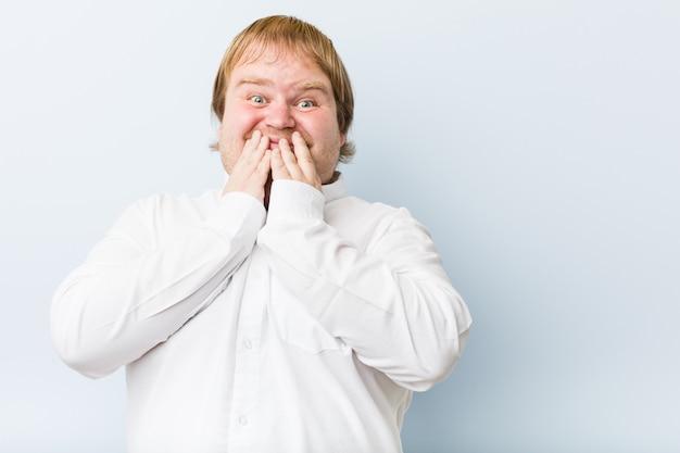 Homem gordo do ruivo autêntico novo que ri sobre algo, cobrindo a boca com as mãos.