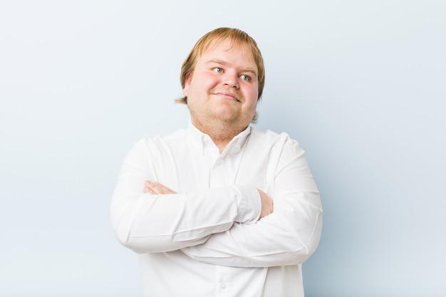 Homem gordo do ruivo autêntico novo que sorri seguro com braços cruzados.