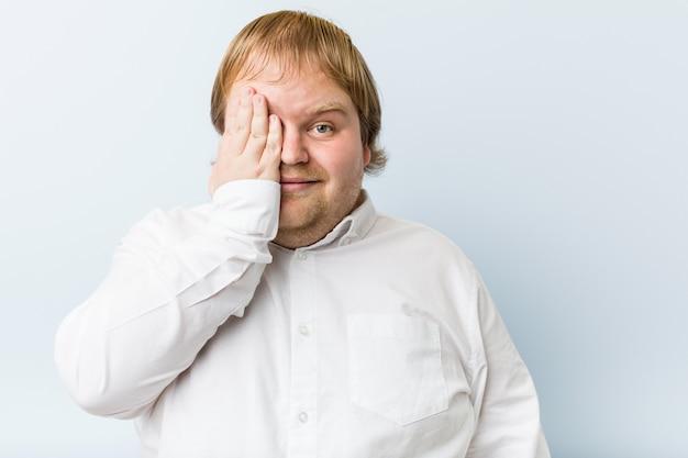 Homem gordo do ruivo autêntico novo que tem o divertimento que cobre a metade da cara com a palma.