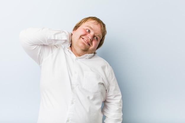 Homem gordo do ruivo autêntico novo que toca atrás da cabeça, pensando e fazendo uma escolha.