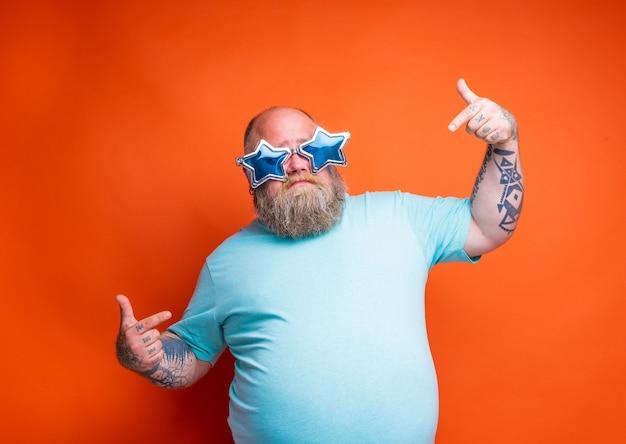 Homem gordo e delirante com tatuagens de barba e óculos escuros não tem certeza de alguma coisa