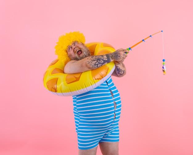 Homem gordo e estressado com peruca na cabeça brincando com a vara de pescar