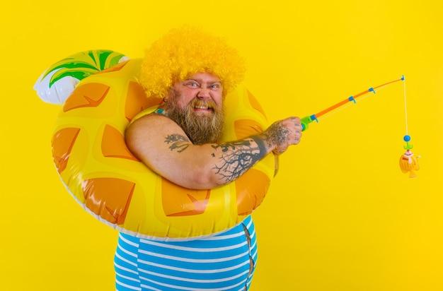 Homem gordo e feliz com peruca na cabeça brincando com a vara de pescar
