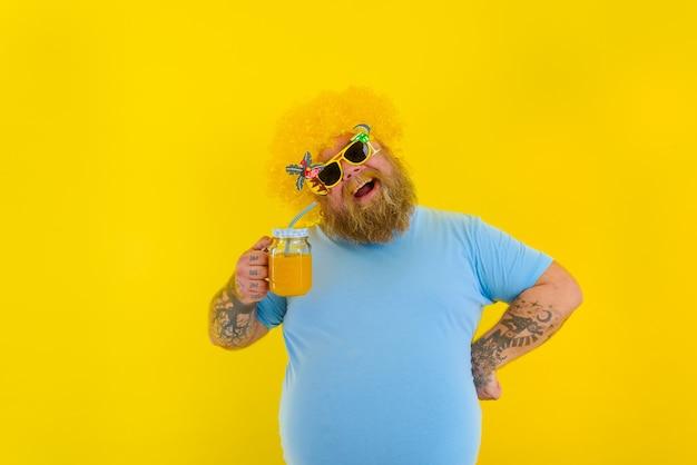 Homem gordo e feliz com peruca na cabeça e óculos escuros bebe um suco de fruta