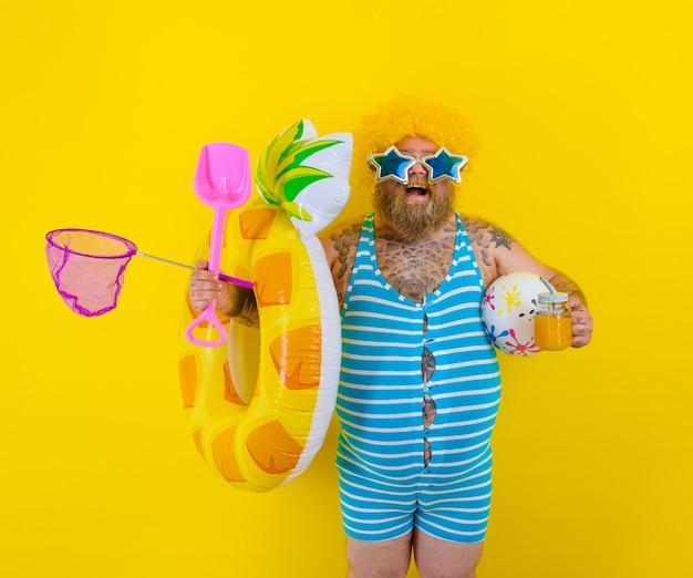 Homem gordo e feliz com peruca na cabeça está pronto para nadar com um salva-vidas de donut