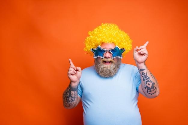 Homem gordo e feliz com tatuagens de barba e óculos de sol dançando música em uma discoteca