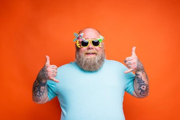 Homem gordo e feliz com tatuagens de barba e óculos de sol está pronto para o verão